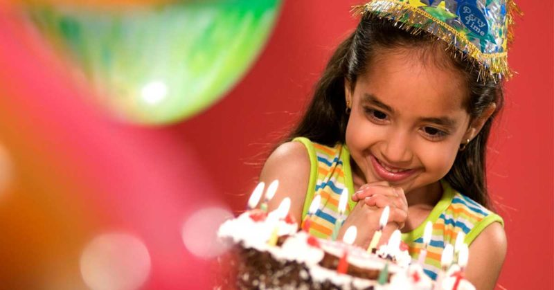 Kid looking at the cake at a birthday party